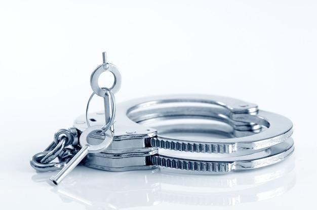 Close-up di manette in metallo e chiave nel buco della serratura isolato