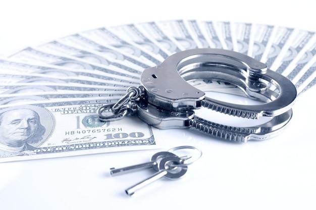 Close-up di manette in metallo, chiavi e dollari americani cash pack isolato su sfondo bianco