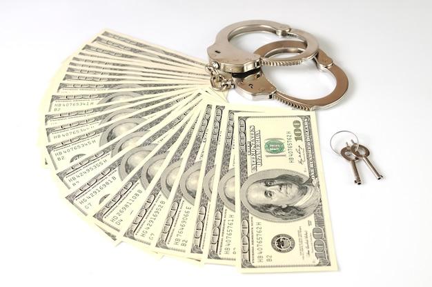 Close-up di manette in metallo, chiavi e dollari americani cash pack isolato