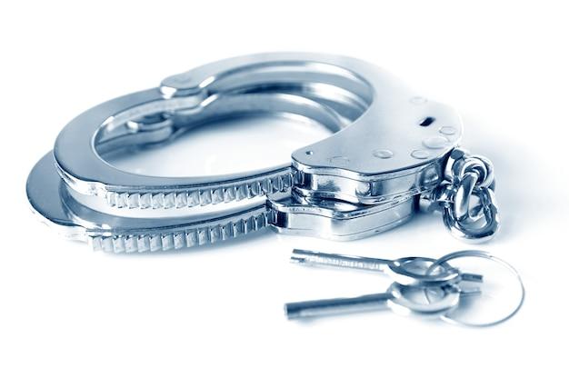 Close-up di manette in metallo e chiavi isolate su sfondo bianco