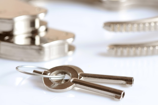 Close-up di manette in metallo e chiavi isolate su superficie bianca. giochi sessuali e pratica del concetto di bdsm