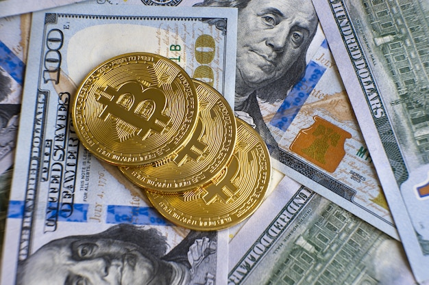 Close up di metallo lucido bitcoin crypto monete di valuta sulle fatture del dollaro usa. concetto di denaro decentralizzato elettronico.