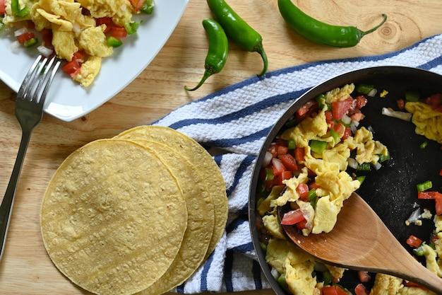 Primo piano di uova messicane in padella, piatto bianco, cucchiaio di legno, tavolo in legno e tortillas