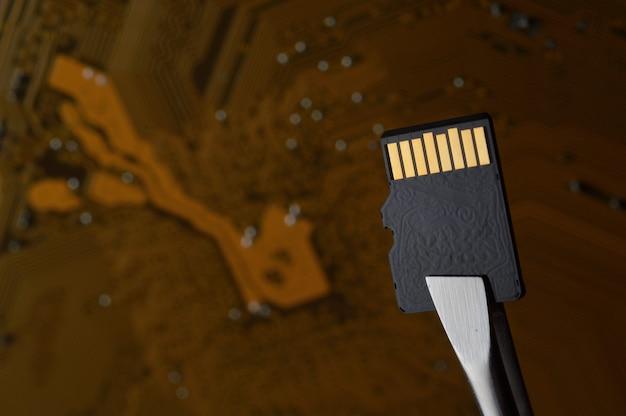 Primo piano di una scheda di memoria micro sd contro un microcircuito, fissata con una pinzetta.