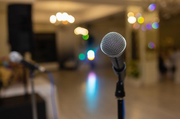 Primo piano del microfono sopra l'estratto sfocato del partecipante nella sala seminari o nella sala conferenze