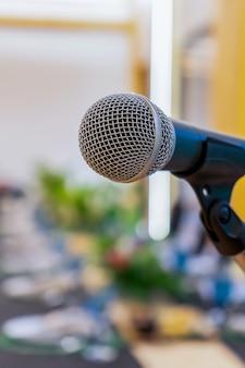 Vicino al microfono accanto al podio con sfocatura del lungo tavolo nero all'ora di cena in una luce calda al tungsteno.
