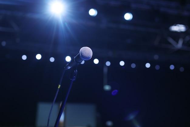 Primo piano del microfono in una sala da concerto o una sala conferenze con luci fredde in sottofondo.