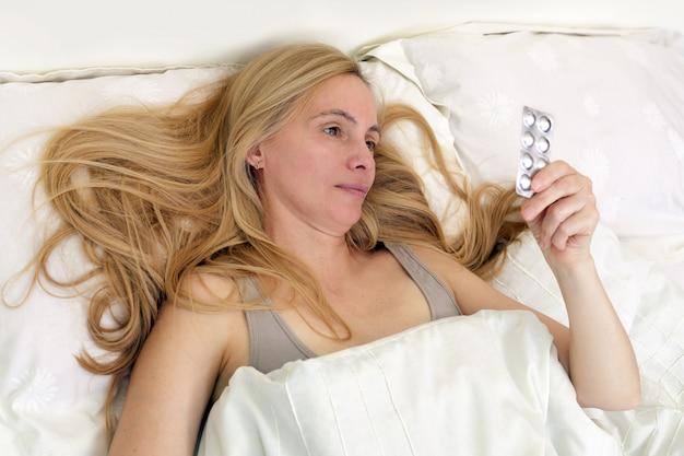 Chiuda in su sulla donna bionda di mezza età a letto