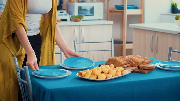 Primo piano di una donna di mezza età e un anziano più anziano si divertono a lavorare insieme apparecchiando la tavola da pranzo in cucina, mentre gli uomini parlano in sottofondo durante una rilassante giornata in famiglia.