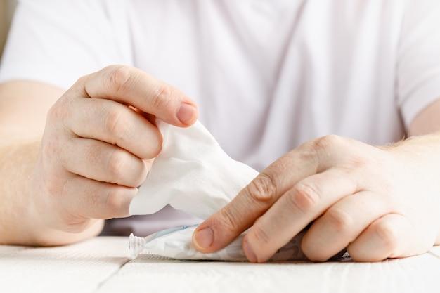Primo piano sul tronco delle mani di un uomo che si pulisce usando il tessuto bianco dell'alcool che pulisce la disinfezione del tovagliolo da virus e batteri nel giorno a casa o in ufficio