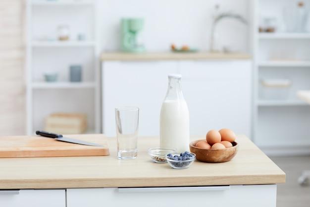Primo piano di uova di latte e frutti di bosco sul tavolo in cucina a casa