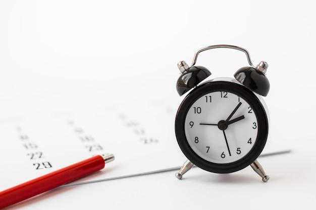 Primo piano di mini sveglia, calendario e penna rossa su bianco