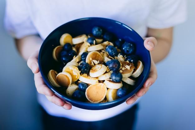 Close-up di cereali mini pancake, mini pancake in una ciotola blu scuro con miele di sciroppo d'acero con mirtillo nelle mani del bambino. sfondo di cibo.