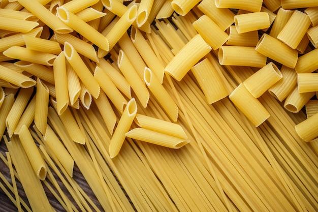 Close up mix di pasta italiana cruda essiccata, maccheroni, spaghetti, penne sul tavolo di legno. vista dall'alto