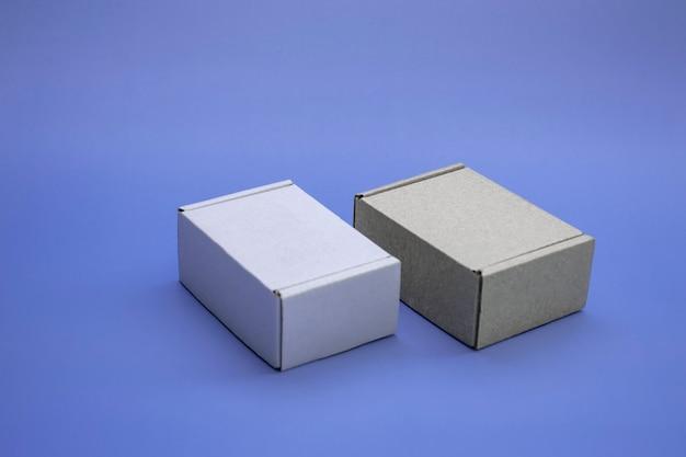 Modello ravvicinato di scatole di cartone con spazio di copia. due scatole di corton: marrone e bianco su sfondo blu. concetto per imballaggio, regali, consegna.
