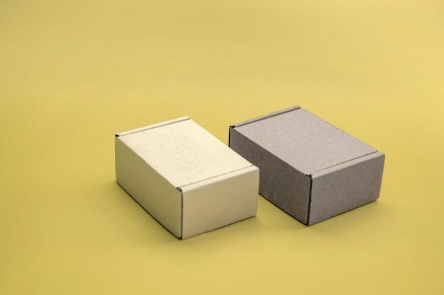 Modello ravvicinato di scatole di cartone con spazio di copia. due scatole di corton: marrone e bianco su sfondo giallo. concetto per imballaggio, regali, consegna.