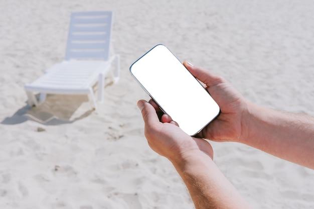 Avvicinamento. mock up smartphone in mani maschili. sullo sfondo della spiaggia e delle sedie a sdraio. concetto di viaggio.