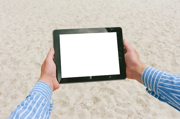 Primo piano, mock up tablet nelle mani di un uomo. sullo sfondo della spiaggia e della sabbia.