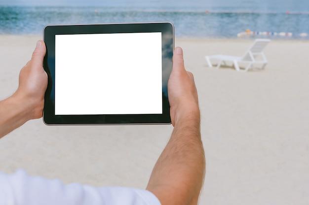 Primo piano mock up tablet in mano maschile. sullo sfondo della spiaggia e delle sedie a sdraio.