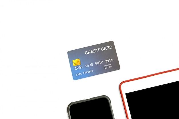 Chiuda su della carta di credito del modello con la compressa e lo smartphone su fondo bianco isolato.