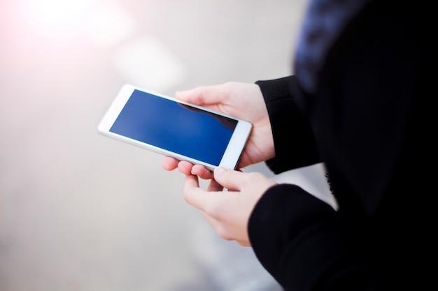 Close up mockup foto di mani femminili con uno smartphone con uno schermo vuoto all'aperto
