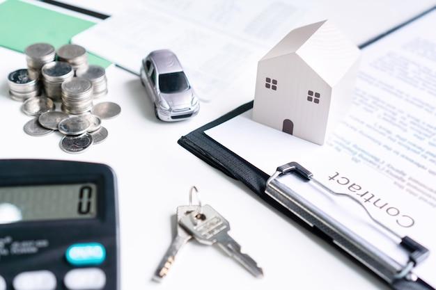 Close up modello di casa e auto, scartoffie, denaro e calcolatrice sul tavolo bianco