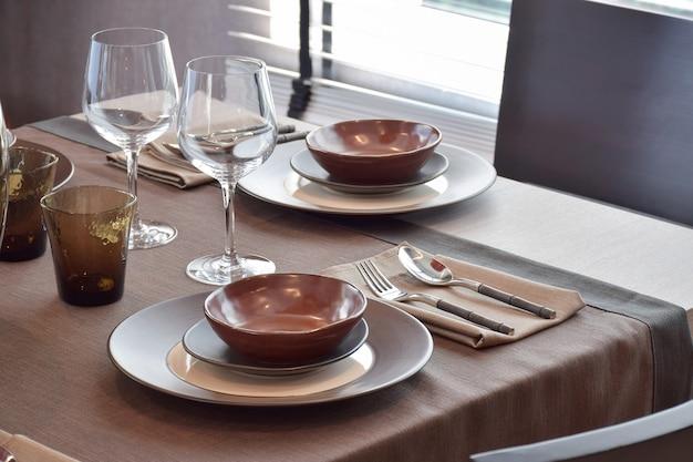 Chiuda sul insieme pranzante classico moderno sul tavolo da pranzo di legno