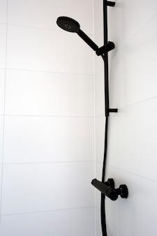 Primo piano del moderno ed elegante soffione doccia nero e vicino al bagno piastrellato bianco in appartamento moderno