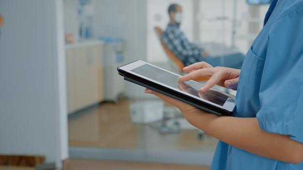 Primo piano di un tablet moderno con touchscreen e mano da infermiere