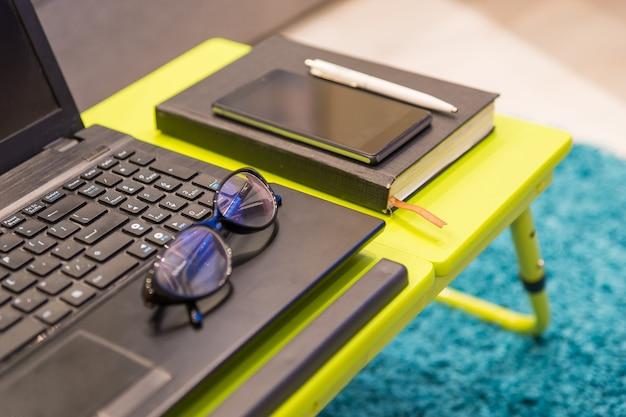 Primo piano di una moderna workstation da tavolo con occhiali eleganti che giace sulla tastiera di un computer portatile aperto con un diario e un telefono cellulare a fianco