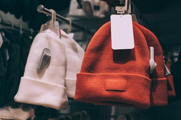 Cappelli invernali in primo piano, moderni con mockup di etichetta, su una vetrina del supermercato.
