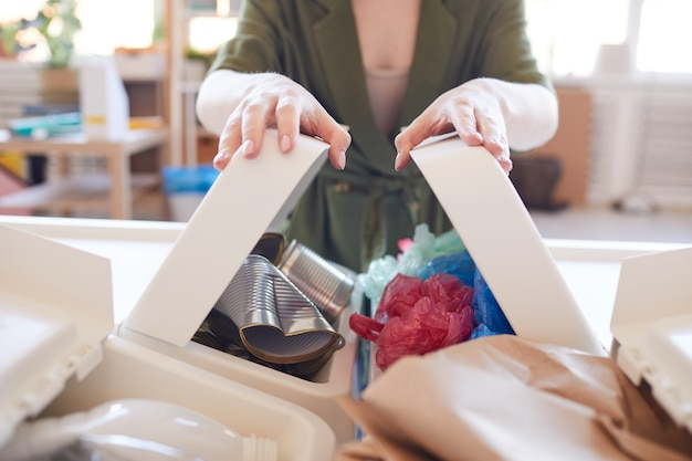 Close up della moderna giovane donna di smistamento dei rifiuti a casa, concentrarsi sui bidoni della spazzatura in plastica in primo piano