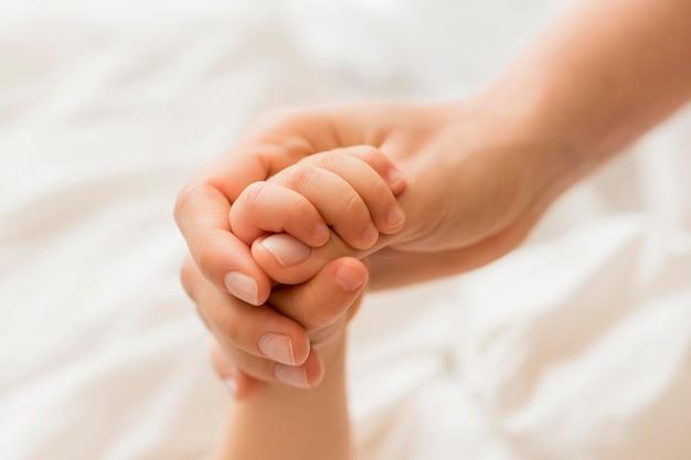 Tenersi per mano della mamma e del bambino del primo piano