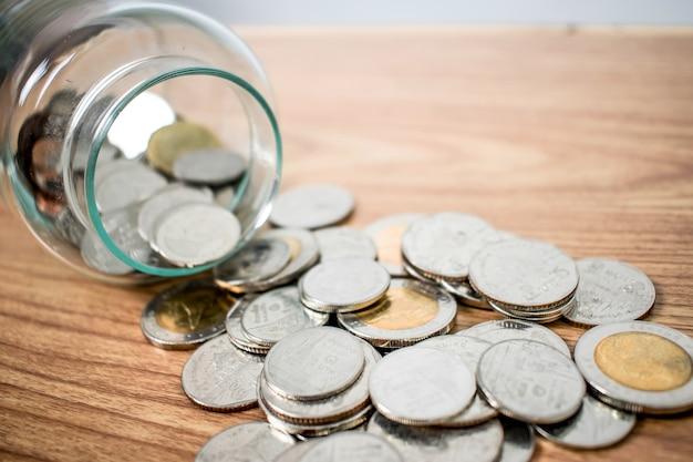 Chiuda su dei baht tailandesi delle monete dei soldi dentro e fuori del barattolo di vetro sulla tavola di legno.