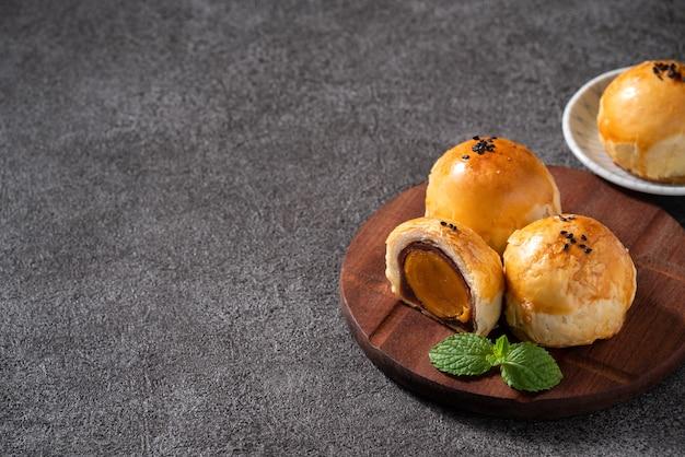 Primo piano di pasta di tuorlo di torta di luna, torta di luna per la festa di mid-autumn festival su sfondo grigio scuro della tabella