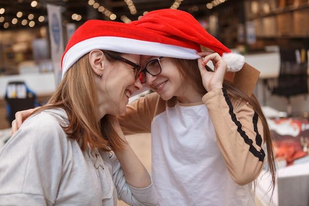 Primo piano di madre e figlia ridendo, toccando la fronte, indossando il cappello di babbo natale