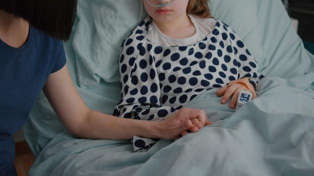 Primo piano della madre che tiene le mani della figlia del bambino malato in attesa del trattamento della malattia
