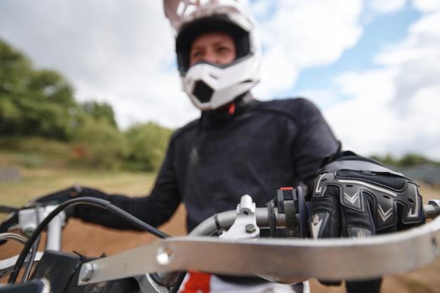 Primo piano del motociclista che tira la frizione mentre si prepara a guidare la pista fuoristrada