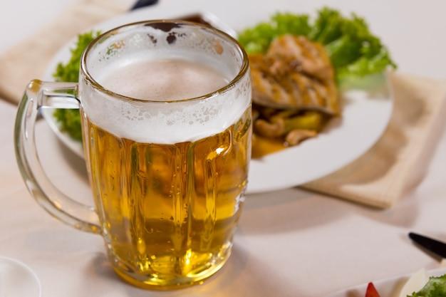 Close up boccale di birra accanto al piatto principale sul tavolo bianco