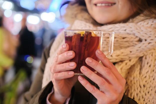 Tazza del primo piano con vin brulè nelle mani della donna