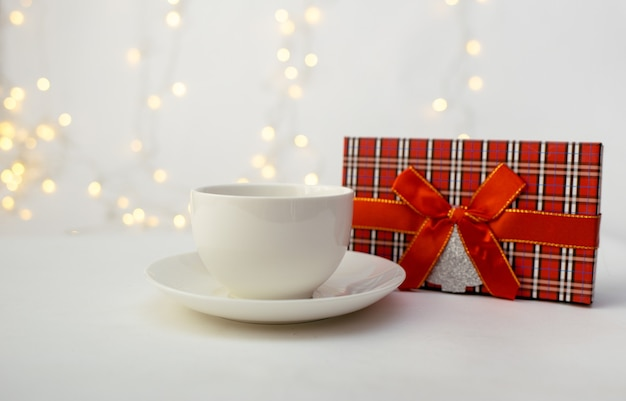 Primo piano di una tazza con un piattino e una confezione regalo rossa su sfondo bianco con un bokeh con un posto per il testo