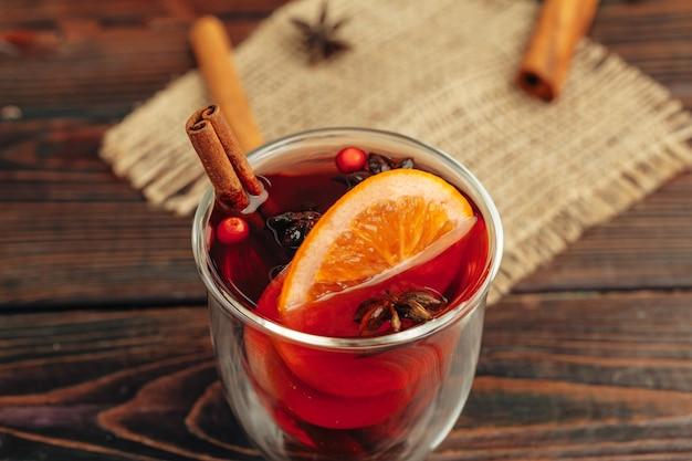 Chiuda in su della tazza di vin brulè con spezie e frutti di bosco sul tavolo grigio