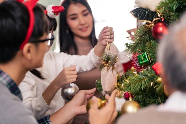 Primo piano famiglia asiatica multigenerazionale che decora insieme un albero di natale