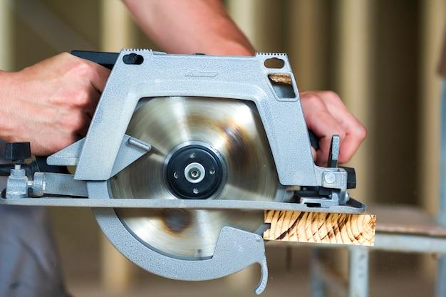 Primo piano delle mani muscolose del carpentiere facendo uso della nuova sega elettrica tagliente potente potente moderna brillante per il taglio del bordo di legno duro. strumenti professionali per la costruzione e il concetto di costruzione.