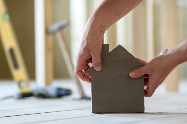 Primo piano delle mani maschii muscolari che tengono piccola casa di modello di legno marrone