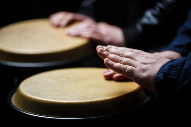 Chiuda in su della mano del musicista che gioca i tamburi dei bonghi.