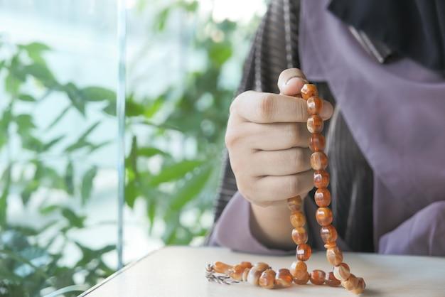 Chiuda in su della mano delle donne musulmane che prega al ramadan.