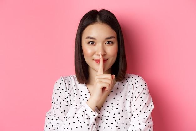 Primo piano di una misteriosa donna asiatica che nasconde un segreto, tace e dice di tacere, in piedi su sfondo rosa