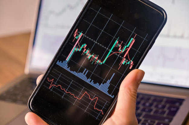 Primo piano di una mano che tiene in mano uno smartphone con grafico a candela per criptovaluta di investimento nel mercato azionario commerciale