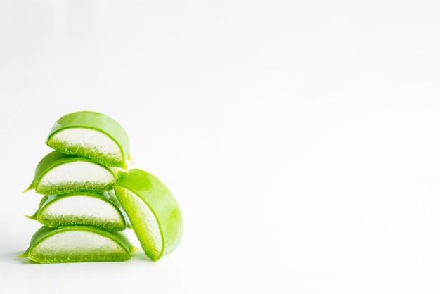 Pianta organica naturale del vera dell'aloe del primo piano affettata per liquido cosmetico casalingo contro fondo bianco.